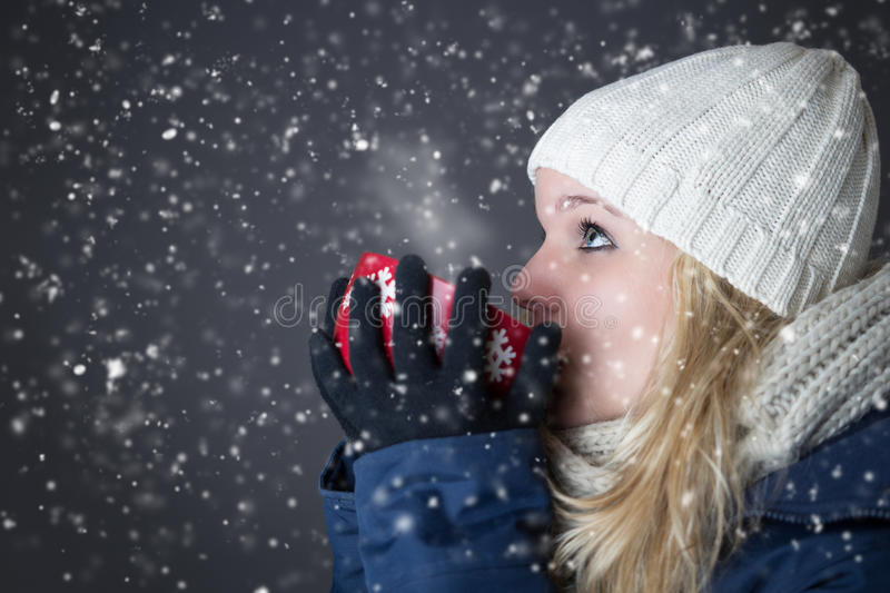 Woman warming up with hot drink. Woman in snow warming up with hot drink stock images