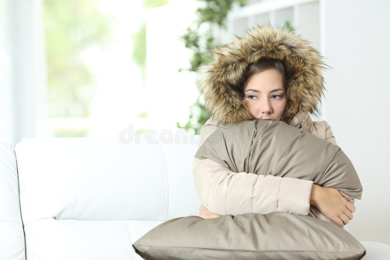 Woman warmly clothed in a cold home. Angry woman warmly clothed in a cold home sitting on a couch royalty free stock photo