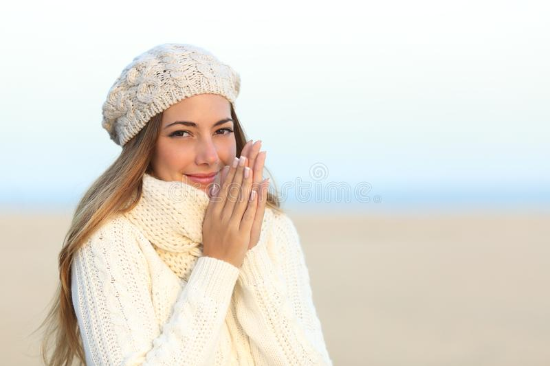 Woman warmly clothed in winter on the beach. Woman warmly clothed in a cold winter on the beach with the sky in the background royalty free stock photos