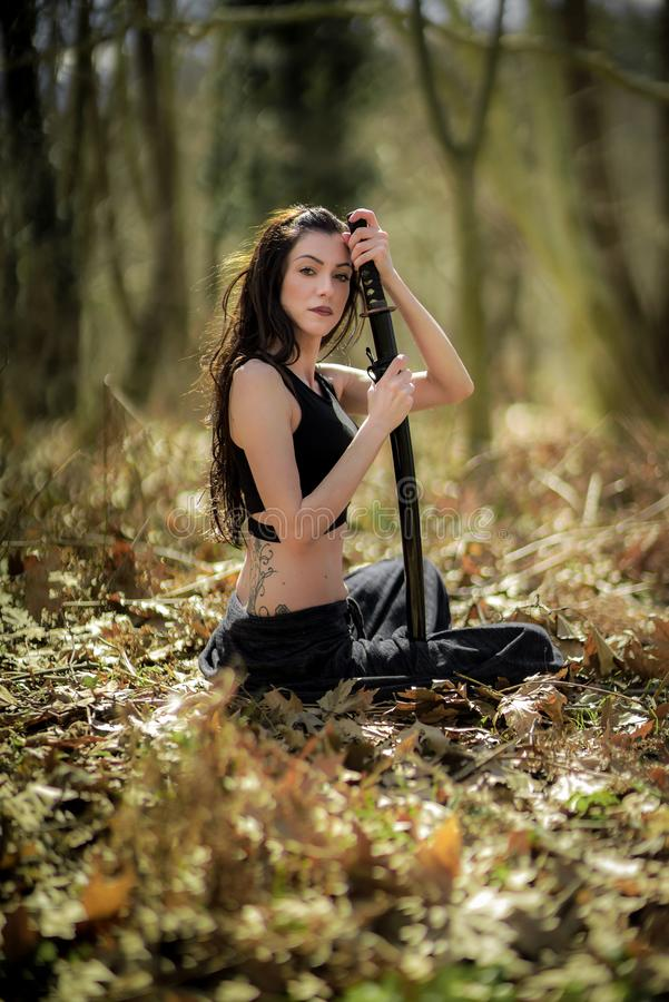 Woman Warrior Holding a Katana Sword, in Mystic Forest royalty free stock photography