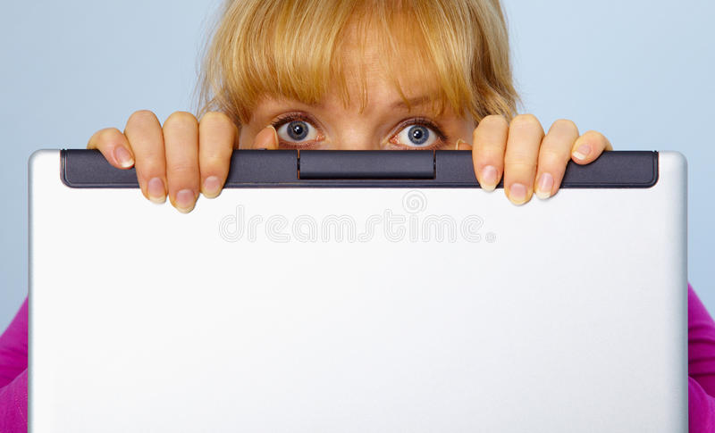 Woman was guilty and hides behind a computer stock photography