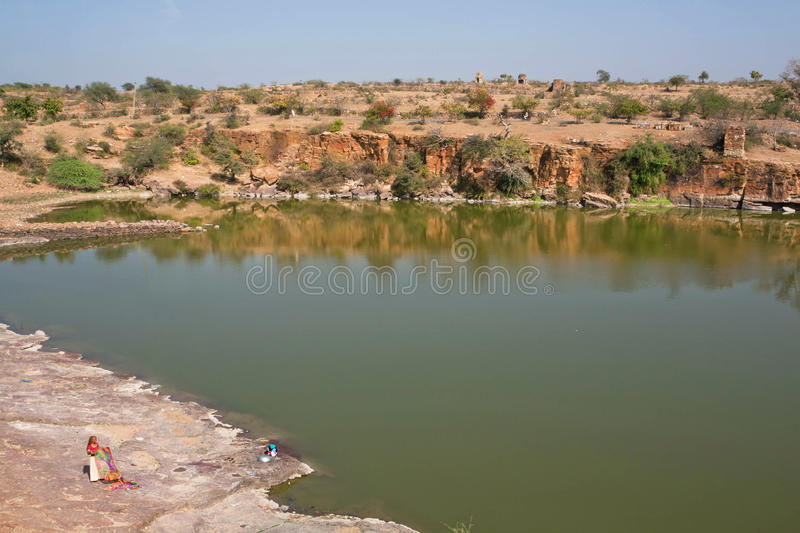 Woman washes clothes in the lake. CHITTORGARH, INDIA: Woman washes clothes in the lake. Chitaurgarh has population about 117,000 and the largest fort in stock images
