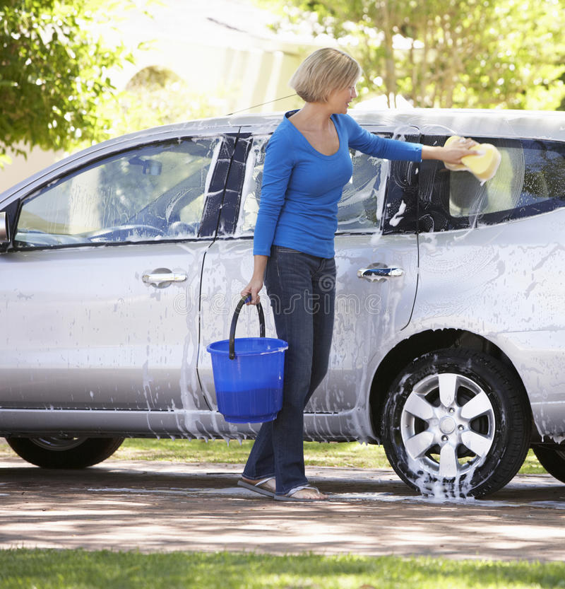 Woman Washing Car In Drive stock photo