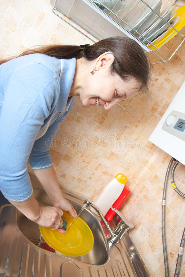 Woman Washing Dishes In Her Kitchen Stock Photo