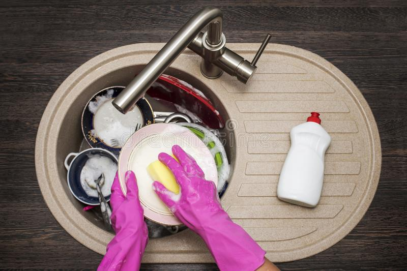 Woman washing dishes in the kitchen. Close up of woman hand. Housewife clean dishes. Housework in the kitchen royalty free stock image