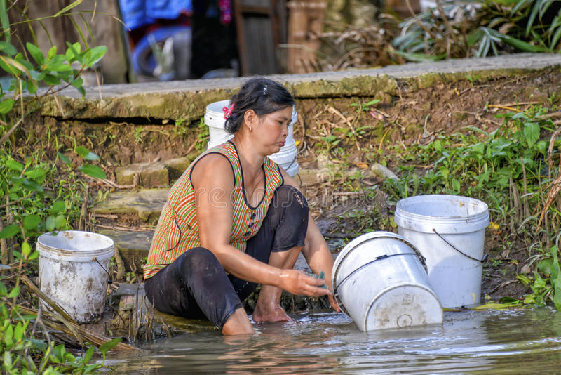 Woman washing dishes in Mekong river royalty free stock photo
