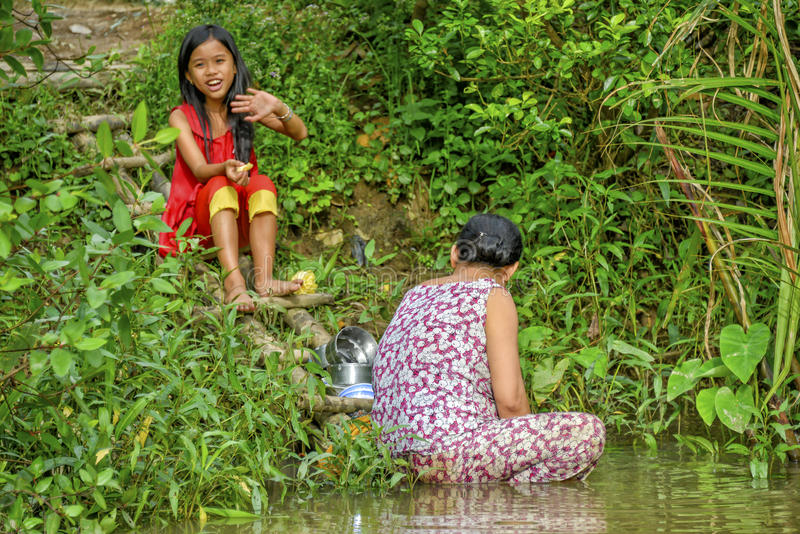 Woman washing dishes in Mekong river stock photography