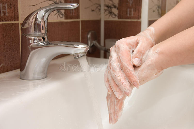 Woman washing hand under running royalty free stock photography