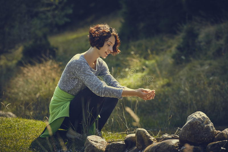 Woman washing hands in mountain stream water stock images