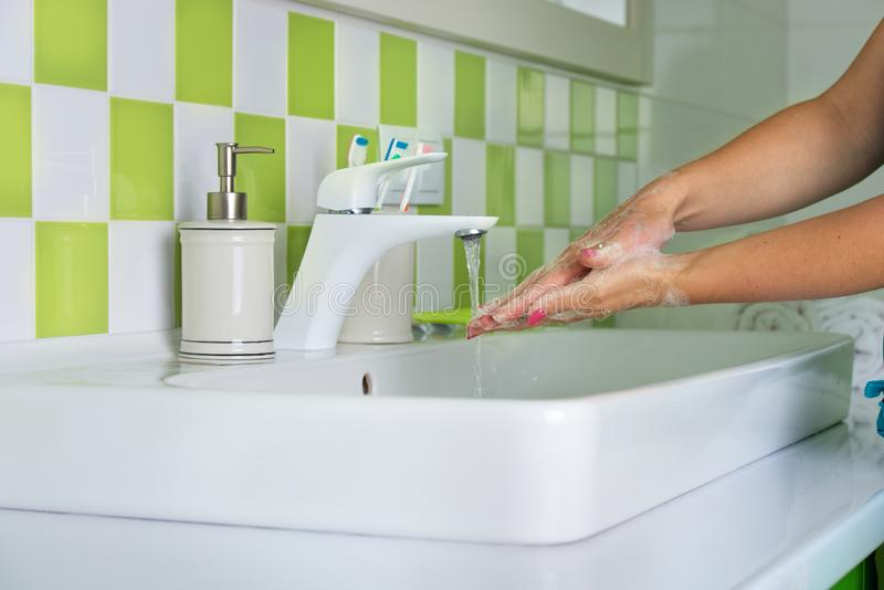 Woman washing hands with soap in the bathroom. stock photos