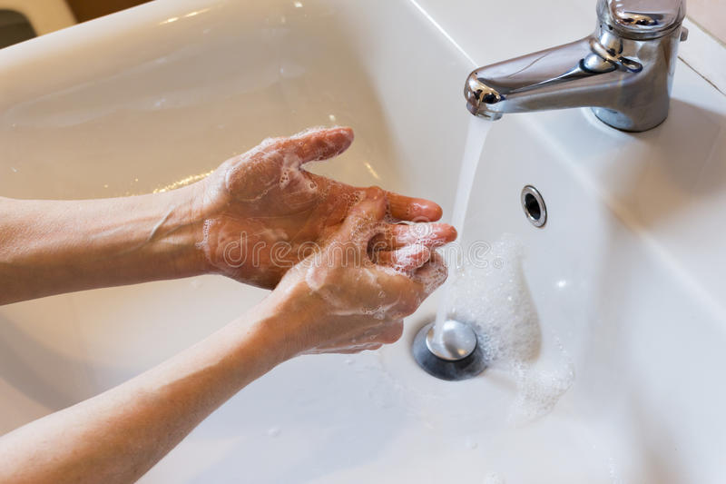 Woman washing hands with soap. In the sink stock images