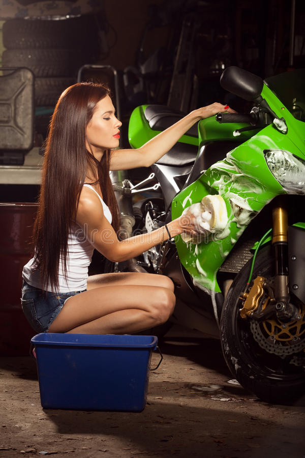 Woman washing motorcycle. In garage and preparing it for a ride royalty free stock images