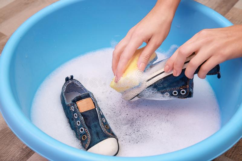 Woman washing sneakers with sponge over plastic basin,. Closeup stock photography