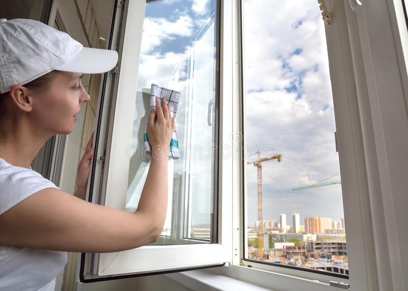 Woman washing the window. Female worker of cleaning company royalty free stock image