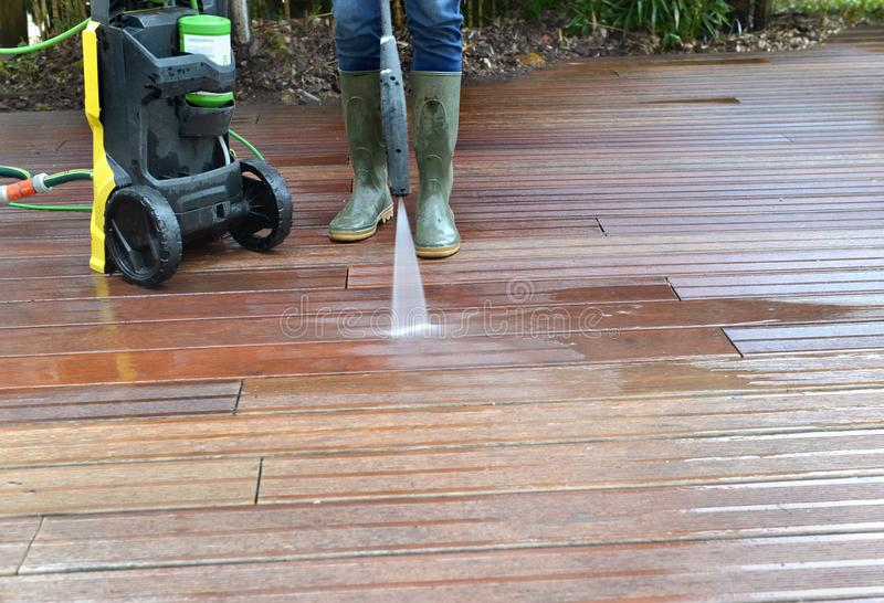 Woman washing wooden terrace with high pressure water stock image