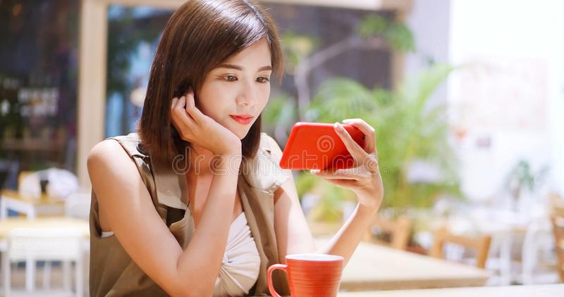 Woman watch video by cellular. In coffee shop royalty free stock photography