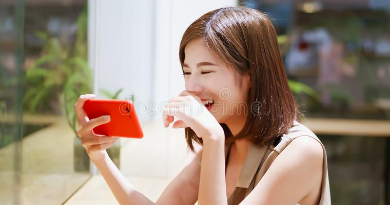 Woman watch video by cellular. In coffee shop royalty free stock photos