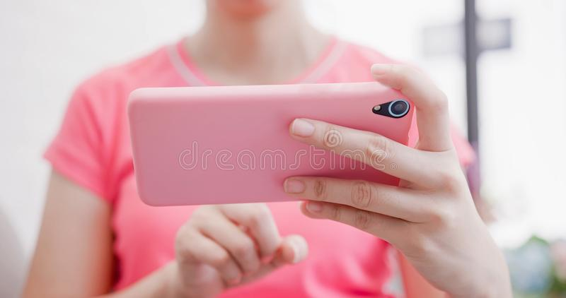 Woman watch video. By smart phone in the room royalty free stock image