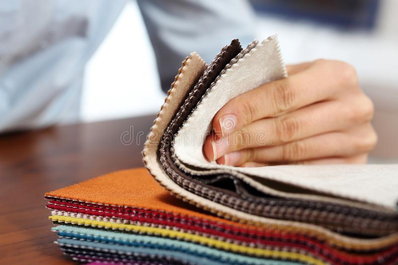 Upholstery fabrics. The woman watches the colors and patterns of upholstery fabrics royalty free stock photos
