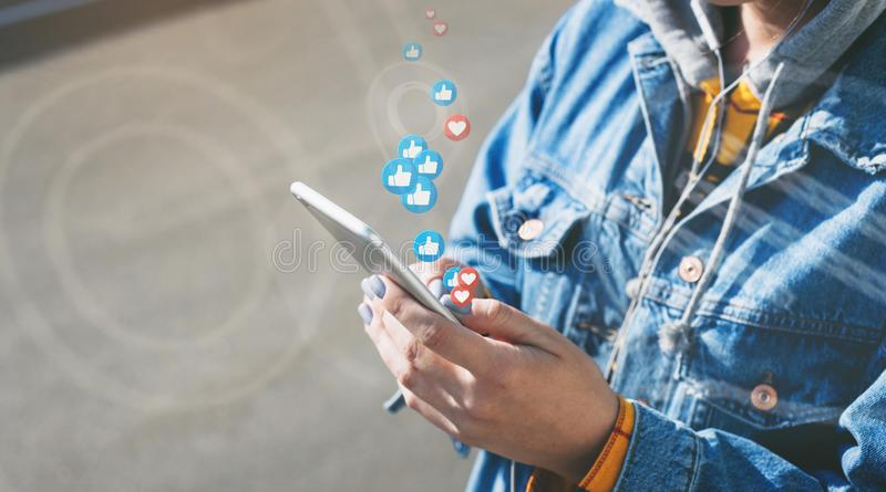 woman watches live stream while walking down city street stock photography