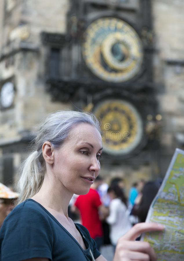 Woman watches the map of the city on background of historical medieval astronomical Clock on the Old Town Hall in Prague, Czech Re stock photos