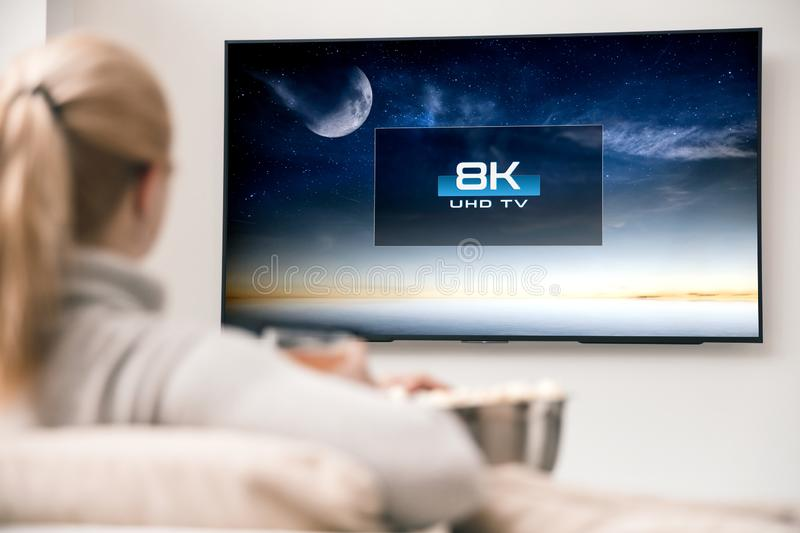 Woman watches tv with 8k ultra hd resolution stock image