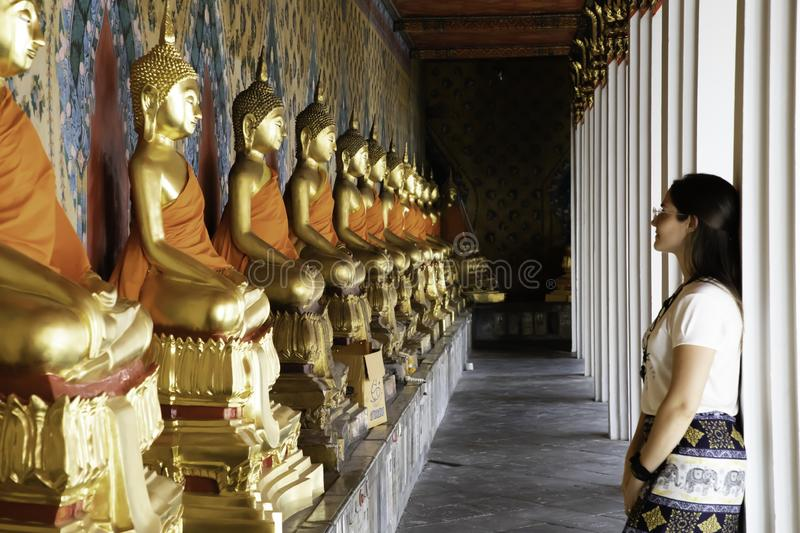 Woman watching aligned golden buddha statues in the Emerald Temple at Bangkok royalty free stock photos