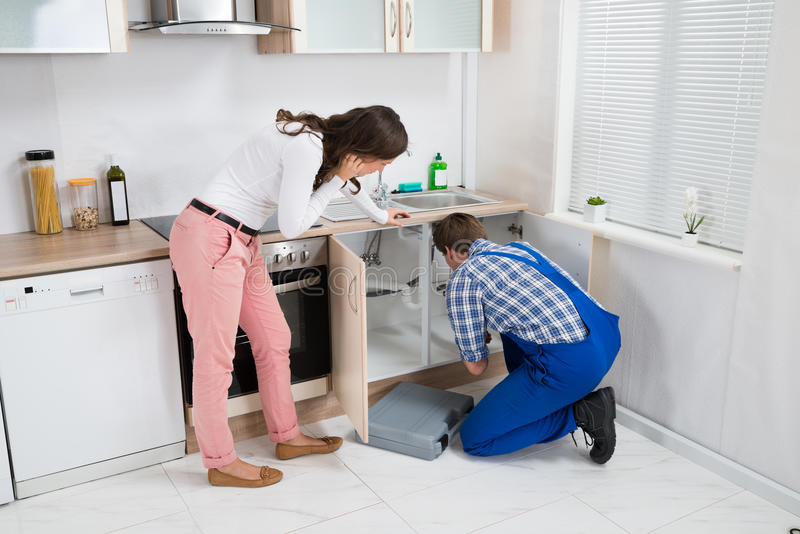 Woman Watching As Worker Repairing Sink Pipe. Young Woman Watching As Worker Repairing Sink Pipe In Kitchen stock images