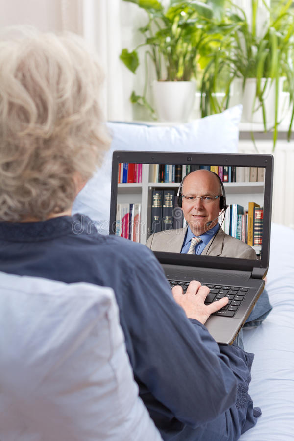 Woman watching english language lesson. Rear view of a senior women sitting relaxed with laptop on her couch, having an online english lesson with her teacher royalty free stock photography