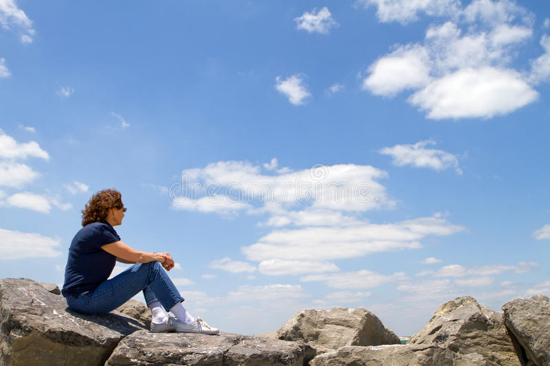Woman Watching From Rocks royalty free stock image