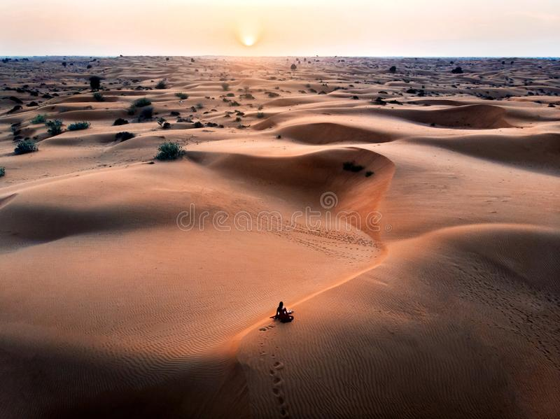 Woman watching sunset in the desert aerial stock image