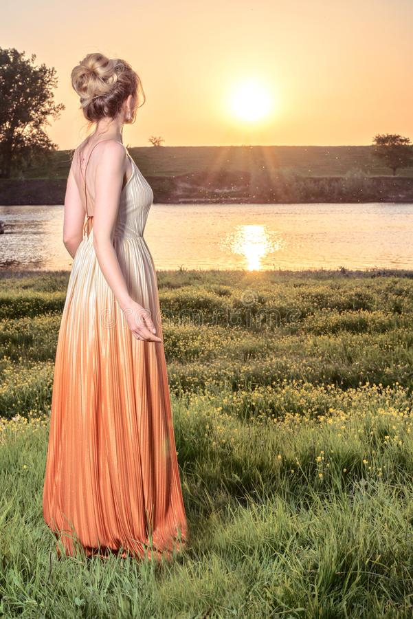 Woman watching the sunset in a long glamorous dress. Beautiful landscapes view, shot from the back royalty free stock images
