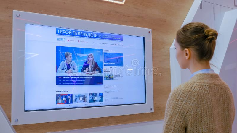 Woman watching TV news on interactive display wall stock image