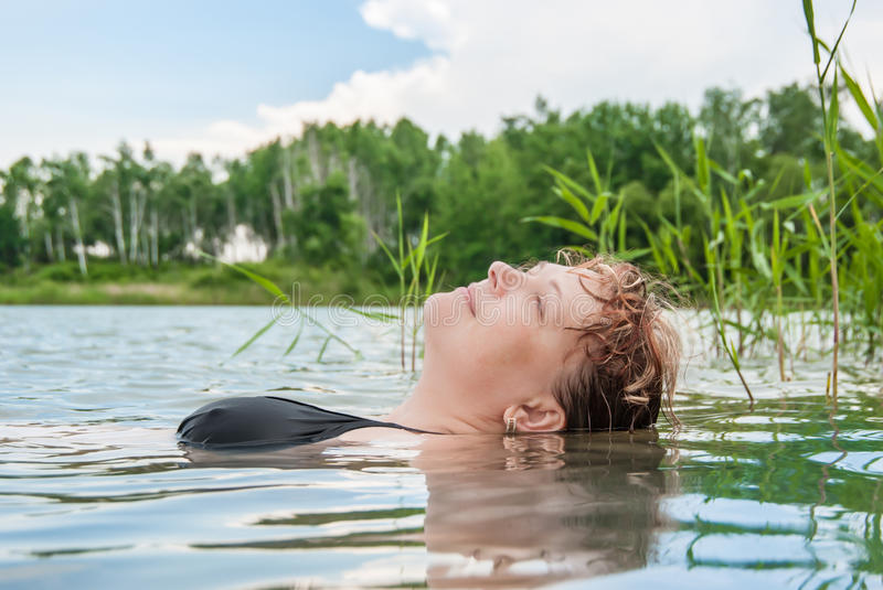 The woman in water. The woman blindly swims in the lake royalty free stock photos