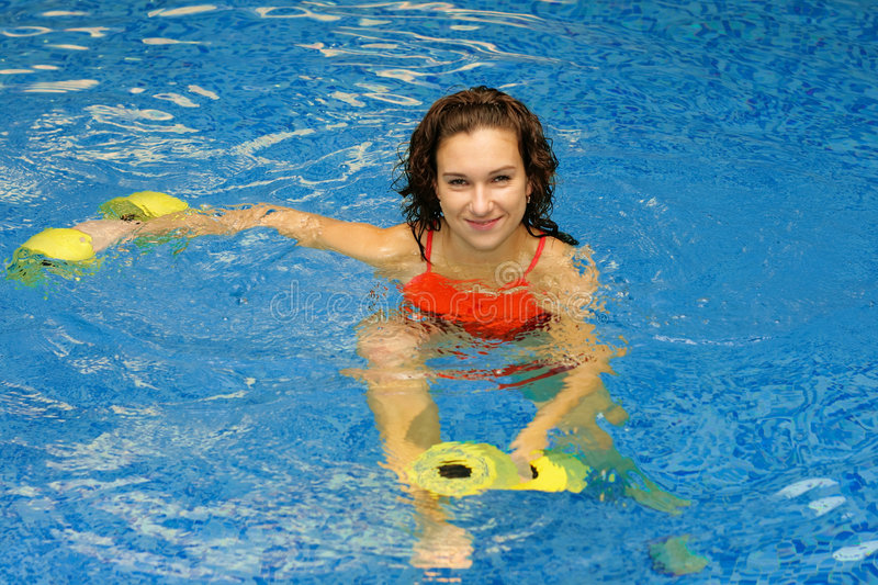 Woman in water with dumbbels royalty free stock image
