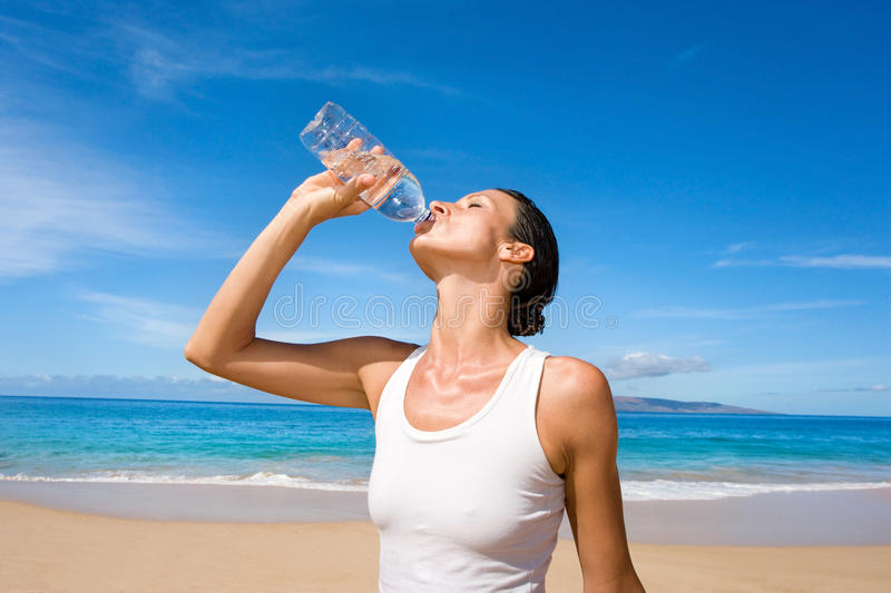 Woman water sport bottle. Woman in white yoga outfit drinking fresh water from sport bottle after exercise stock images