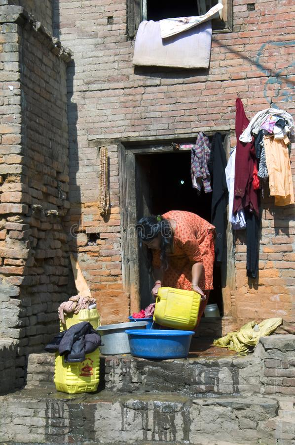 Woman and water. Bhaktapur , Nepal - February 14, 2017: A woman pours water from a can in the basin on the porch of her city house. The photo shows problems stock photo