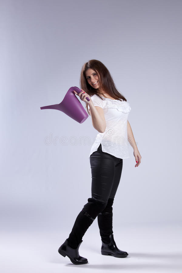 Woman with a watering can. Happy young woman holding a watering can royalty free stock photos
