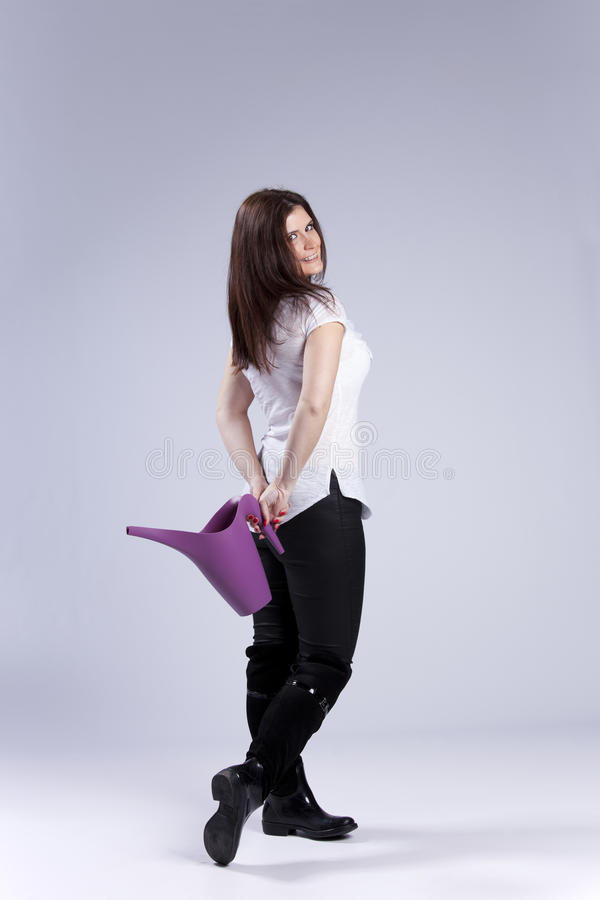 Woman with a watering can. Beautiful woman with a watering can stock images