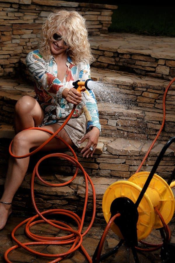 Woman watering with garden hose. Beautiful woman having fun with garden hose splashing summer rain stock images
