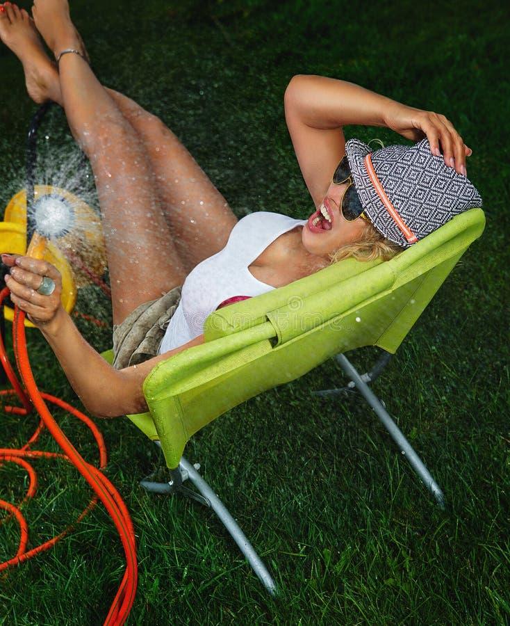 Woman watering with garden hose. Beautiful woman having fun with garden hose splashing summer rain stock photos