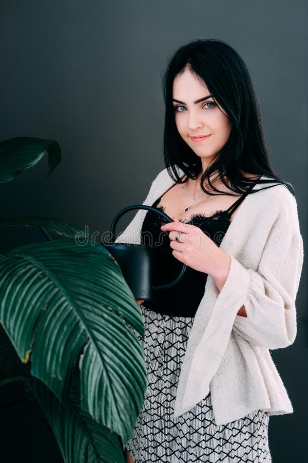 Woman watering pot flowers in the offiice stock photography