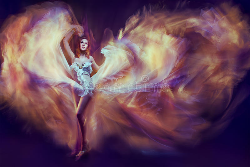 Woman in waving dress as a flame dancing with flying fabric. Dar. Woman in waving dress as a flame dancing with flying fire fabric. Dark background stock photo