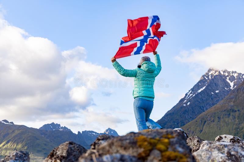Woman with a waving flag of Norway on the background of nature stock photography