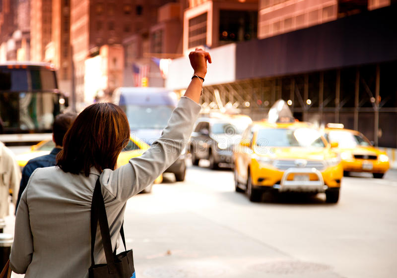 Woman waving for taxi royalty free stock images