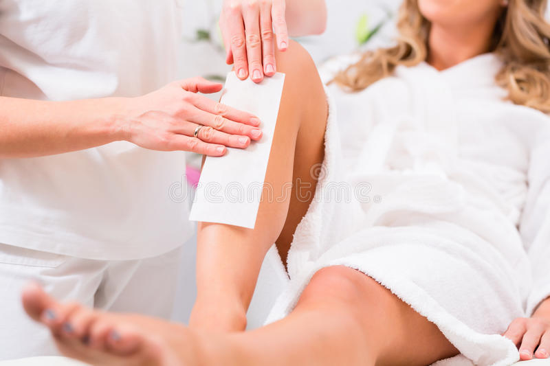 Woman at waxing hair removal in beauty parlor. Woman receiving waxing for hair removal in beauty parlor stock images