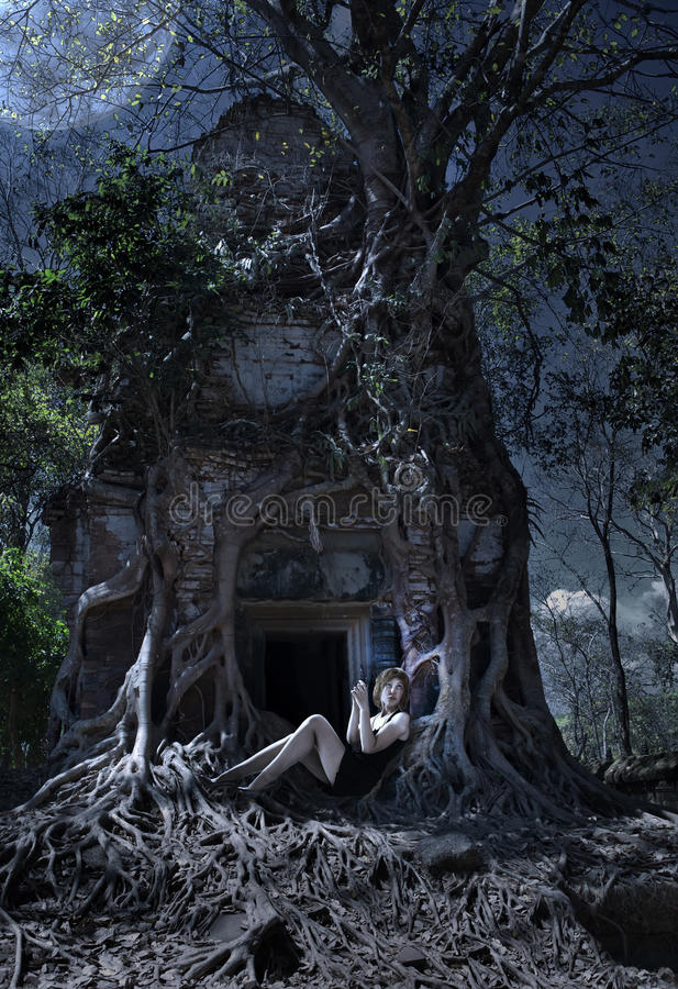 The woman with the weapon at an entrance to the thrown temple in the jungle, night, Cambodia royalty free stock photo