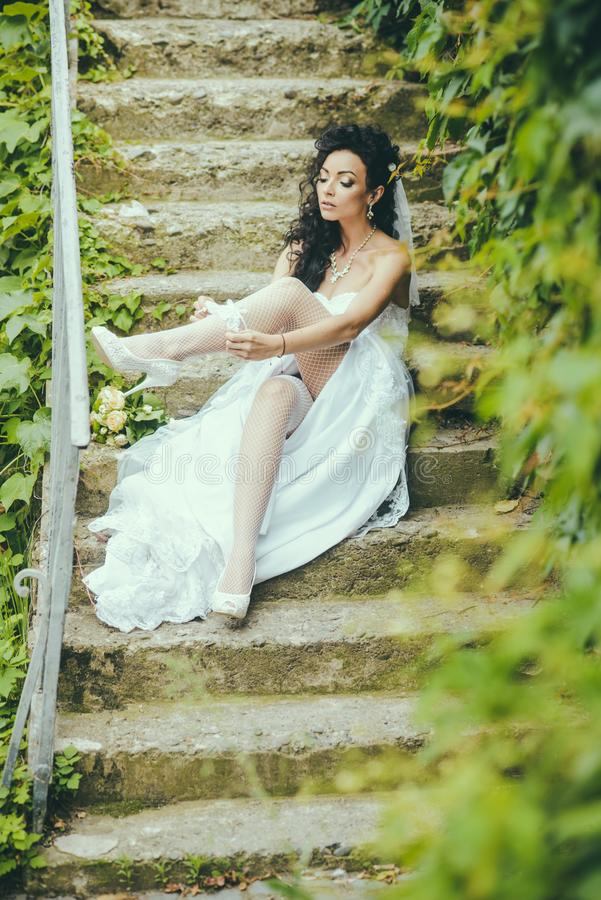 Woman wear lace garter on leg. woman in stockings lingerie on wedding day. Girl with bridal makeup and hairstyle. Bride in white dress sit on steps outdoor stock photography