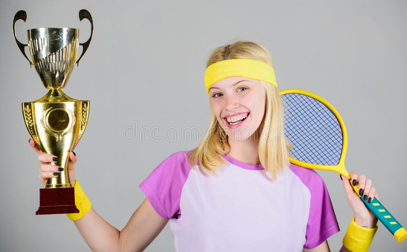 Woman wear sport outfit. First place. Sport achievement. Celebrate victory. Tennis champion. Athletic girl hold tennis. Racket and golden goblet. Win tennis royalty free stock photo