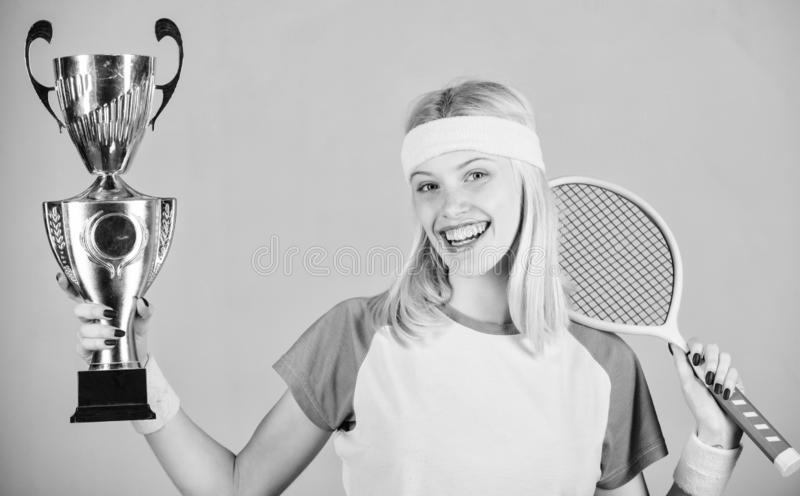 Woman wear sport outfit. First place. Sport achievement. Celebrate victory. Tennis champion. Athletic girl hold tennis. Racket and golden goblet. Win tennis royalty free stock photography